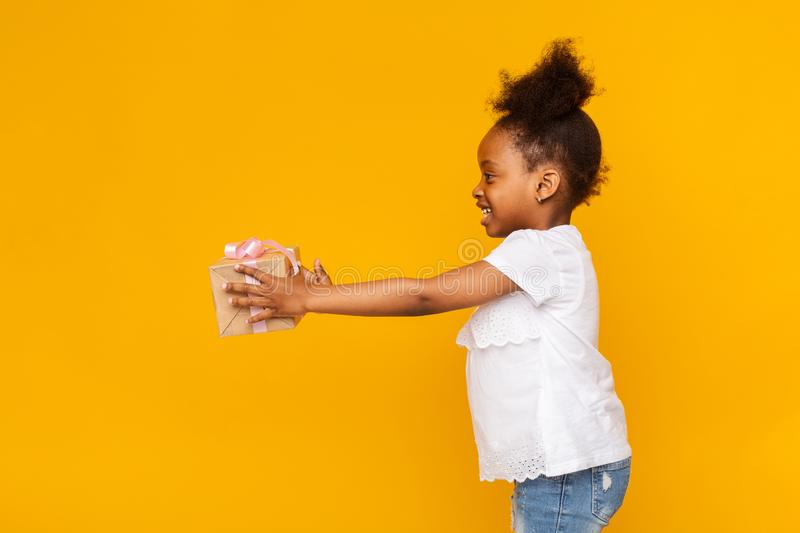 Adorable little african american girl reaching gift box aside stock photo