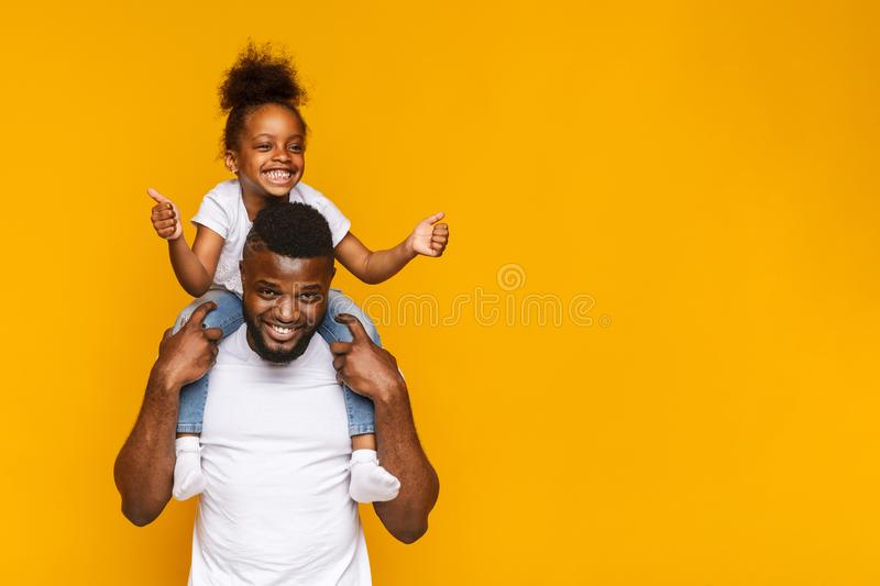 Adorable little african girl gesturing thumbs up on daddy`s shoulders royalty free stock photography