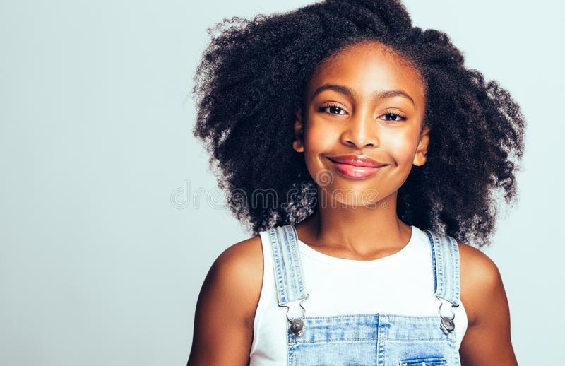 Adorable little African girl smiling against a gray background stock photography
