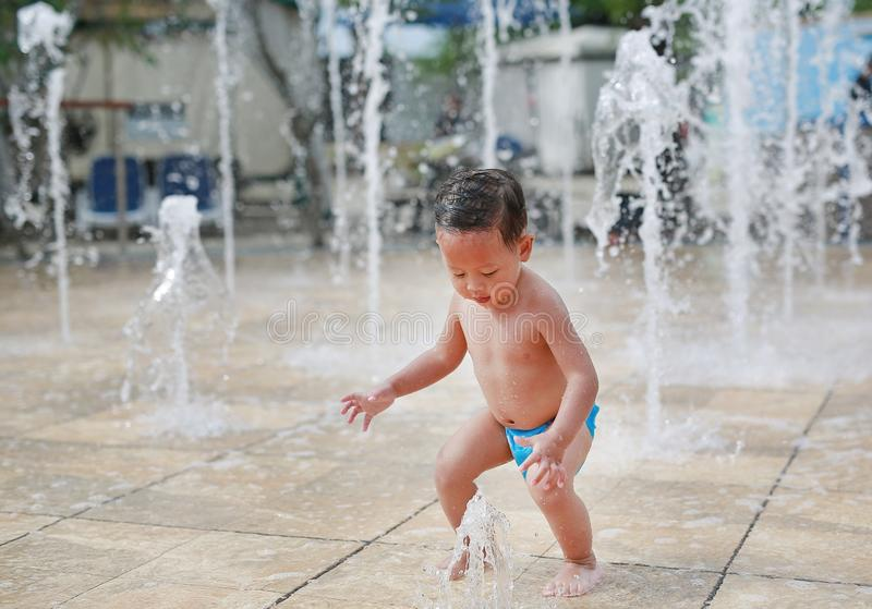 Adorable little Asian baby boy having fun on water stream of a sprinkler. Kid playing in playground fountain in aqua park royalty free stock photos