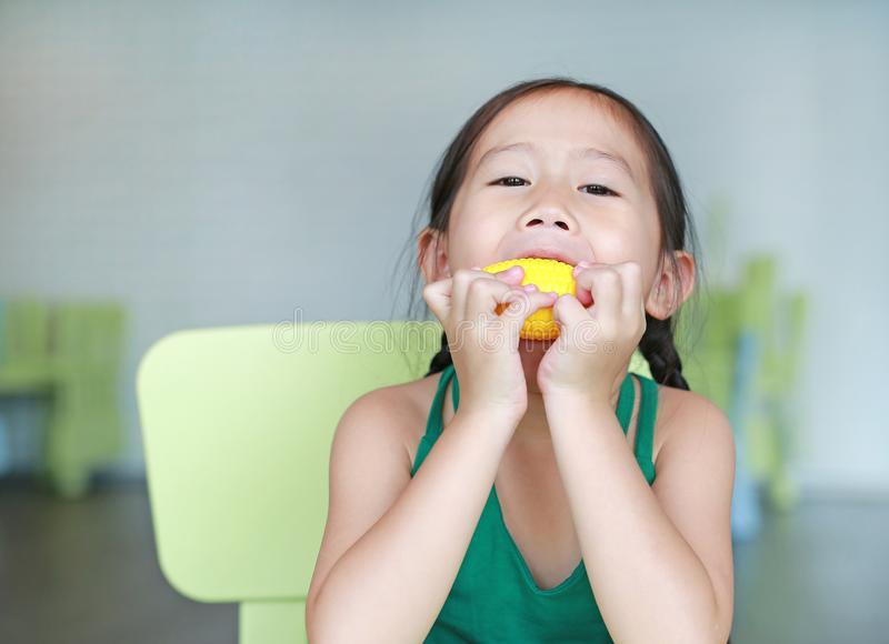 Adorable little Asian child girl playing to eating plastic corn in kid room stock photography