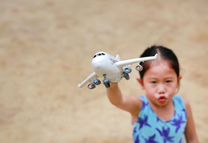 Adorable little Asian child girl playing with a toy airplane in the garden stock image