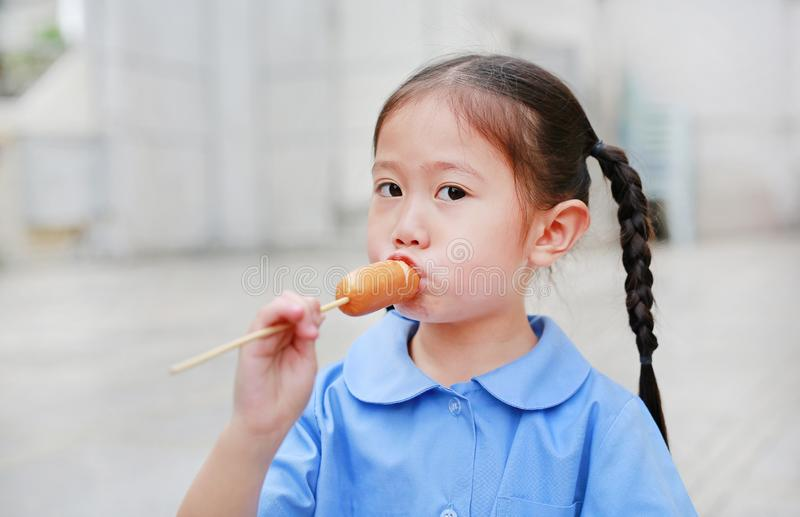 Adorable little Asian child girl in school uniform enjoy eating sausage.  stock photography