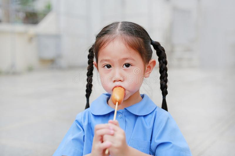 Adorable little Asian child girl in school uniform enjoy eating sausage royalty free stock photography