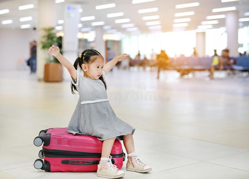 Adorable little asian girl at airport sitting on suitcase with open arm stock photo
