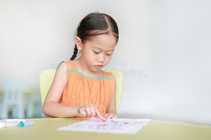 Adorable little Asian girl drawing and painting with water color on paper in children room stock photo