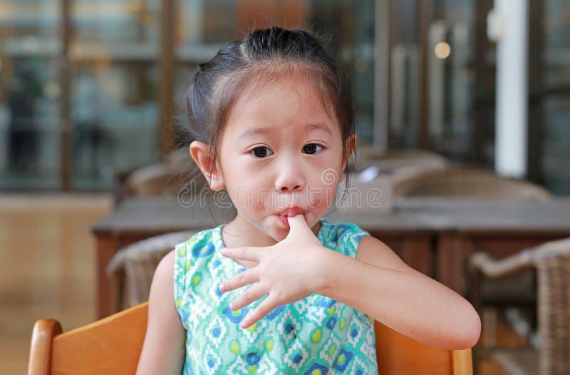 Adorable little Asian girl eating bread. Child having breakfast stock image