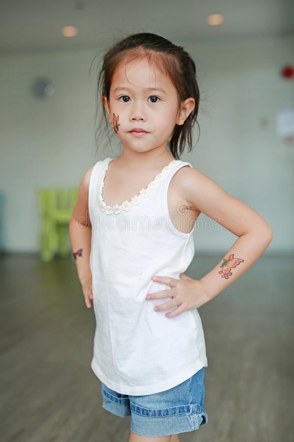 Adorable little Asian kid girl with butterfly tattoo sticker on cheek and arms, Dress up tattoos.  royalty free stock image