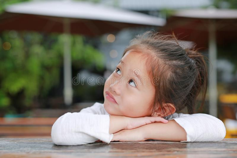 Adorable little Asian kid girl with funny face with looking up lying on the wooden table stock photography