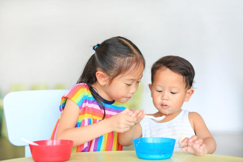 Adorable little Asian sister and her little brother eating cereal with cornflakes and milk together and friendly on the table. royalty free stock photos