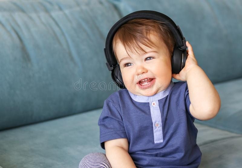 Adorable little baby boy listening to music in headphones on his head sitting on blue sofa at home. And smiling with his first eight teeth, musical education stock photo