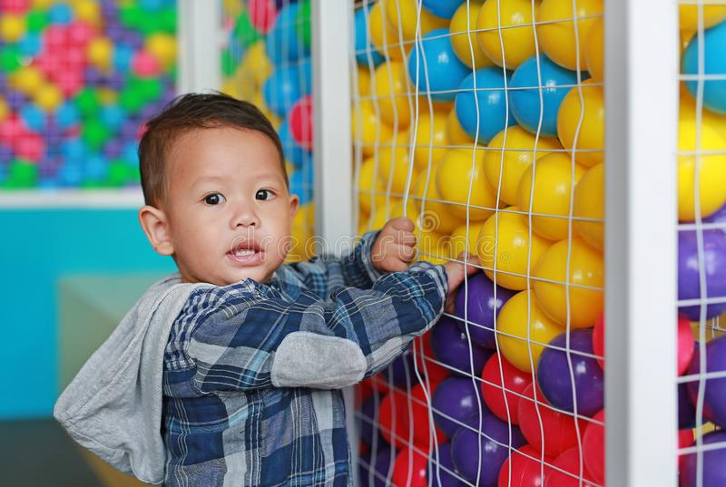 Adorable little baby boy playing colorful plastic ball in cage with looking camera royalty free stock photography