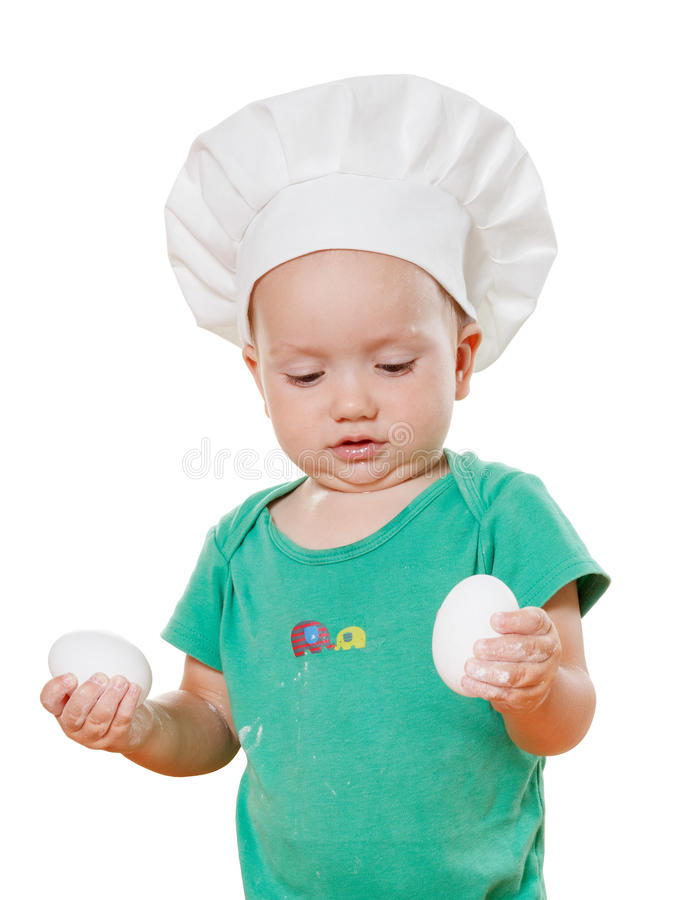 Adorable little baby in a chef's hat, preparing meal of eggs. Isolated on white stock photo