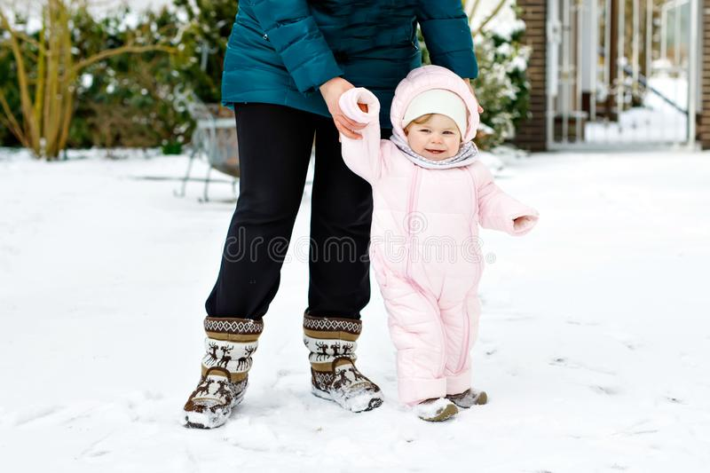 Adorable little baby girl making first steps outdoors in winter with mother. Cute toddler learning walking. Adorable little baby girl making first steps royalty free stock images