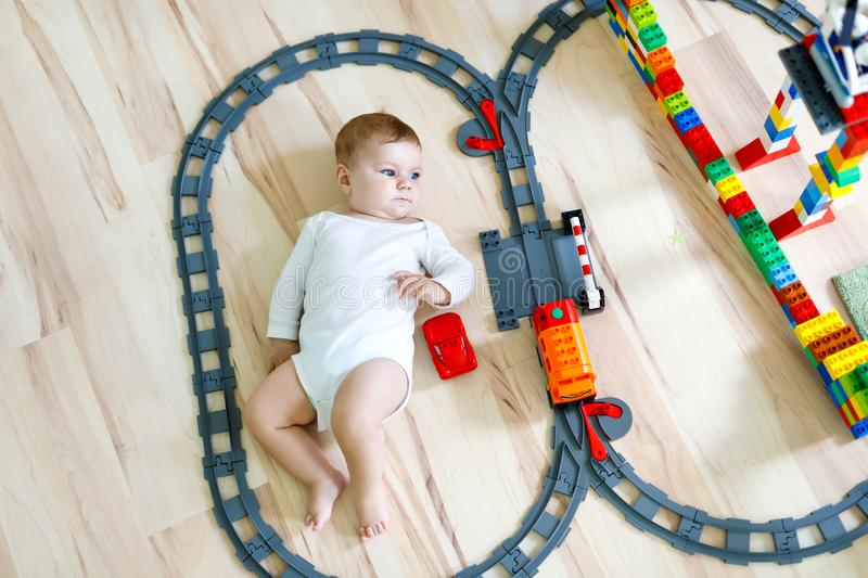 Adorable little baby girl playing with colorful plastic blocks and creating train station royalty free stock photo