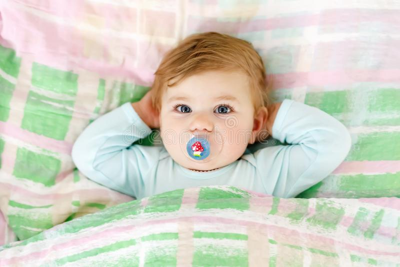 Adorable little baby girl after sleeping in bed. Calm peaceful child with a pacifier or dummy royalty free stock photo