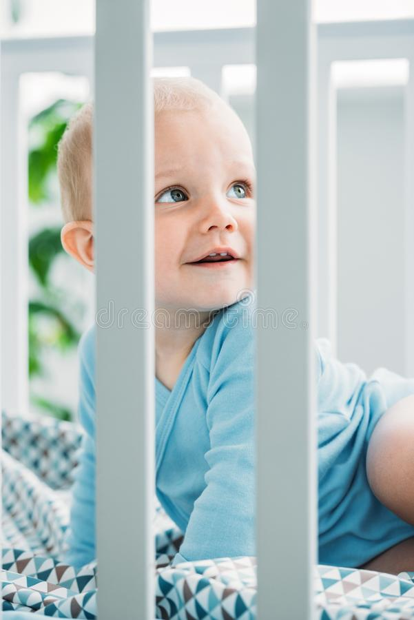 Adorable little baby lying in crib. And looking away stock photo