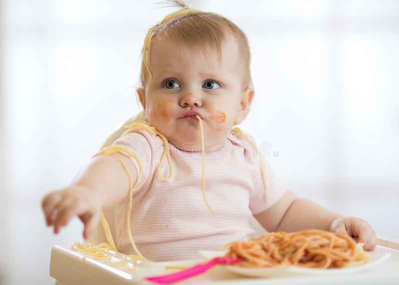Adorable little baby one year eating pasta indoor. Funny toddler child with spaghetti. Cute kid and healthy food. royalty free stock photo