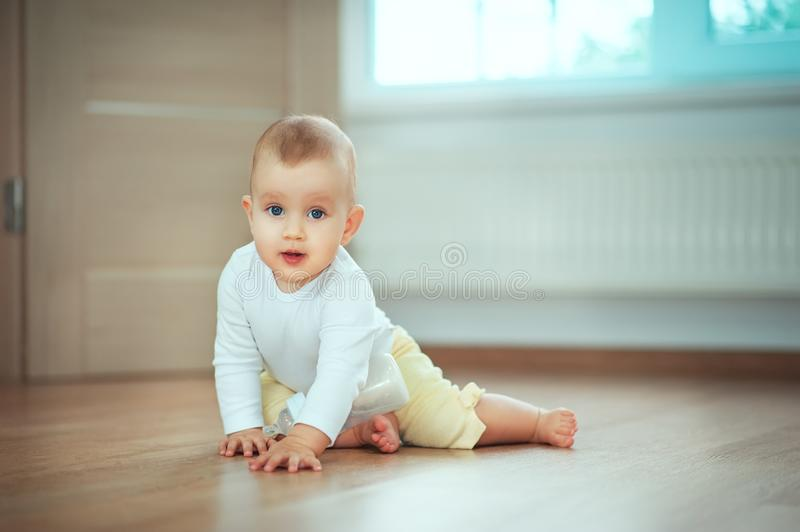 Adorable little baby sitting in bedroom on the floor with bottle with milk or water and laughing. Infant Childhood Kids People stock photo