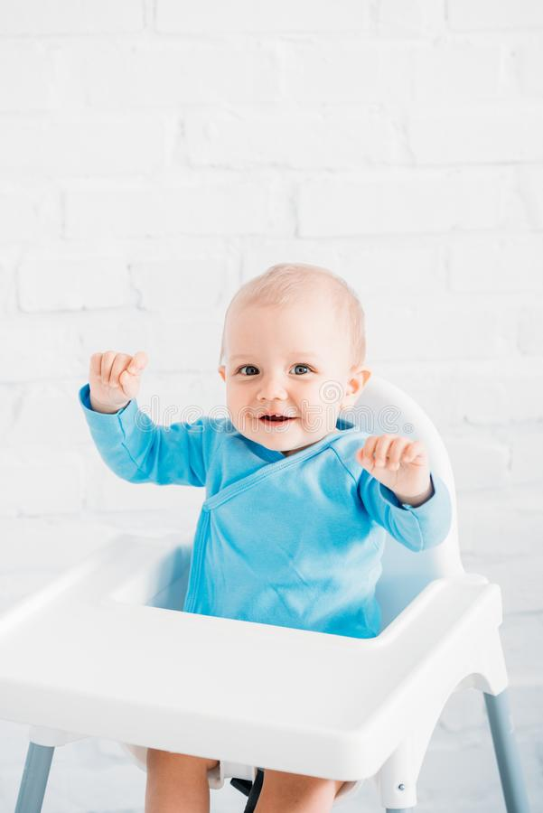 Adorable little baby sitting in high chair in front of white brick wall. Raised hands royalty free stock photography