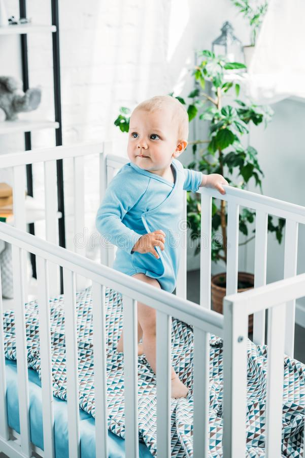 Adorable little baby standing in crib. And looking away stock image