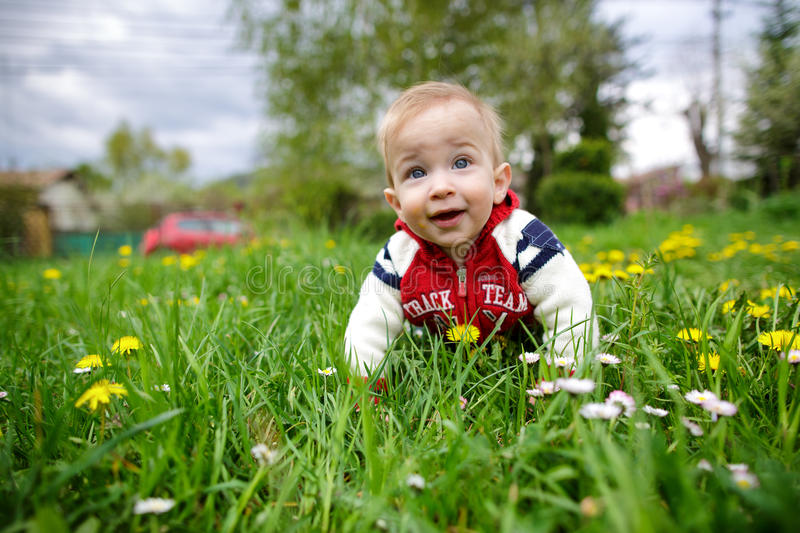 Adorable little blond child with blue eyes laying on the grass royalty free stock photo