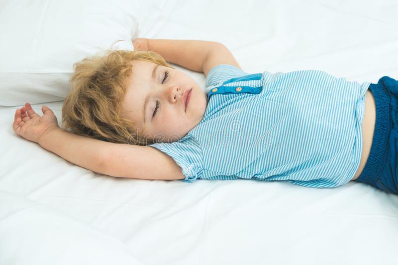 Adorable little blond kid boy in clothes sleeping and dreaming in his white bed. Healthy child with soft bad, peaceful royalty free stock images