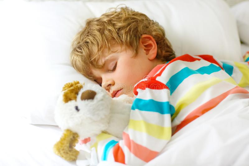 Adorable little blond kid boy in colorful nightwear clothes sleeping and dreaming in his white bed with toy. healthy stock photography