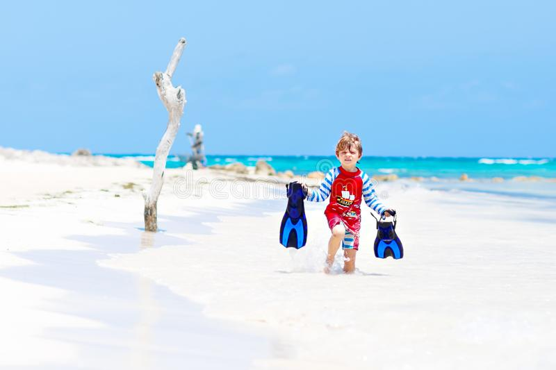Adorable little blond kid boy having fun on tropical beach of Maldives. Excited child playing and surfing in sun stock photography