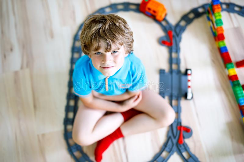 Adorable little blond kid boy playing with colorful plastic blocks and creating train station. Child having fun with stock images