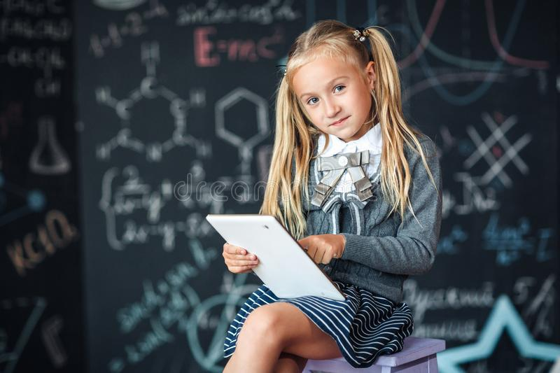 Adorable little blond schoolgirl in school uniform holding white digital tablet. Chalkboard with school formulas background. Back royalty free stock photos