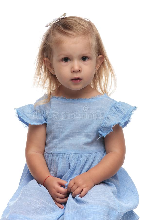 Adorable little blonde girl in blue dress sits on chair royalty free stock photo
