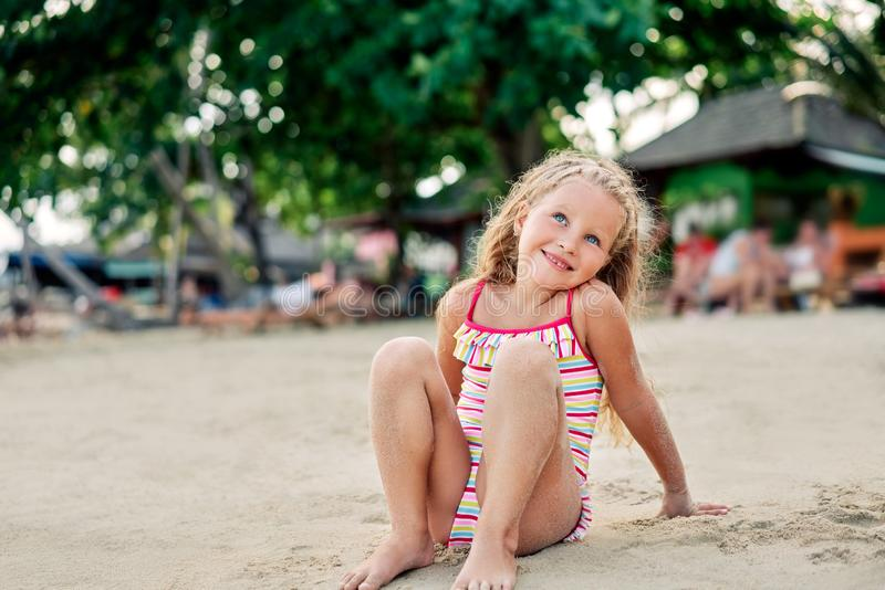 Adorable little blonde girl relax on sandy beach enjoy sea stock images