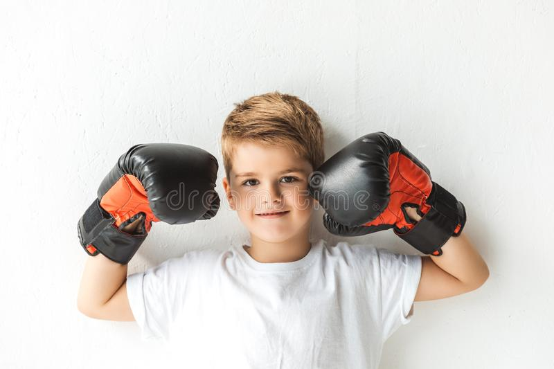 adorable little boy in boxing gloves smiling at camera stock images