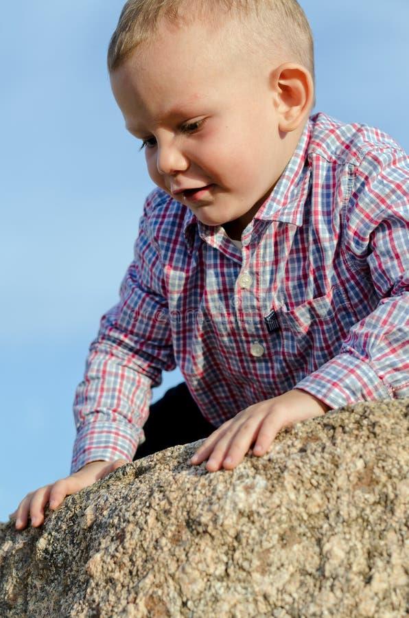 Adorable little boy climbing a rock stock photos