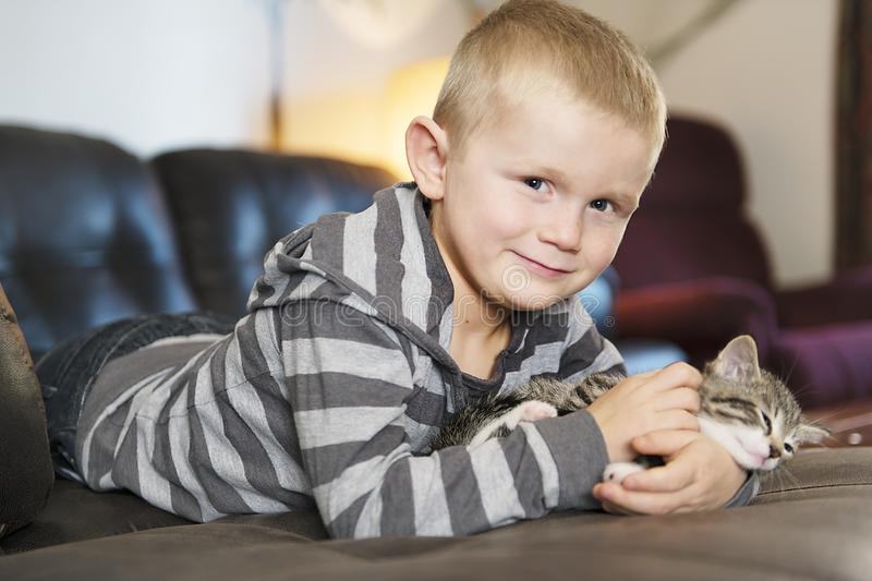 Adorable little boy with cute cat on sofa. An adorable little boy with cute cat on sofa royalty free stock image