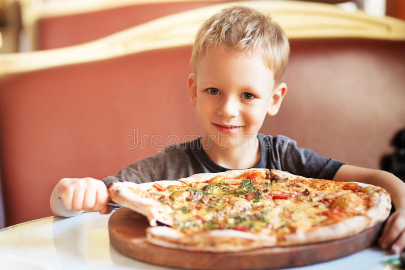 Adorable little boy eating pizza at a restaurant royalty free stock photography