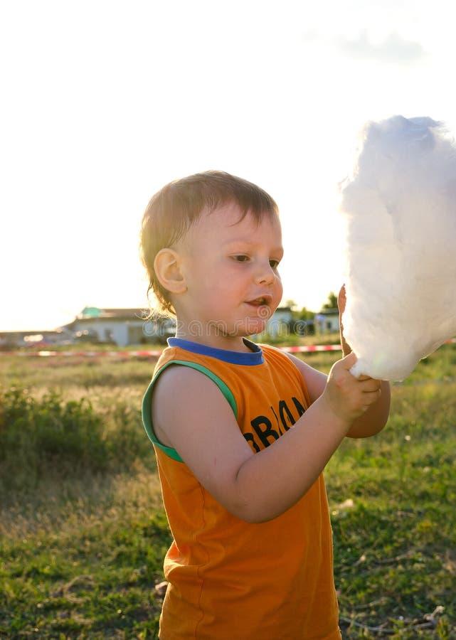 Adorable little boy enjoying cotton candy royalty free stock image