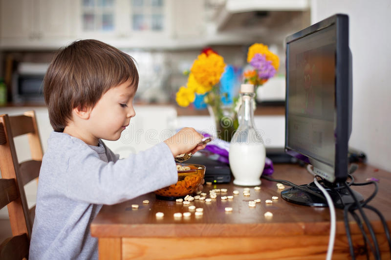 Adorable little boy, having cereals for breakfast while watching. Cartoon on computer royalty free stock image