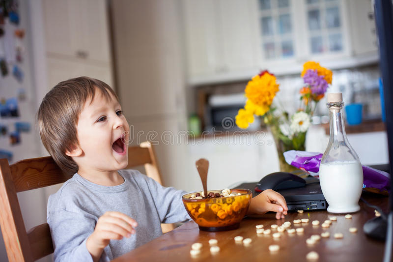Adorable little boy, having cereals for breakfast while watching. Cartoon on computer stock photography