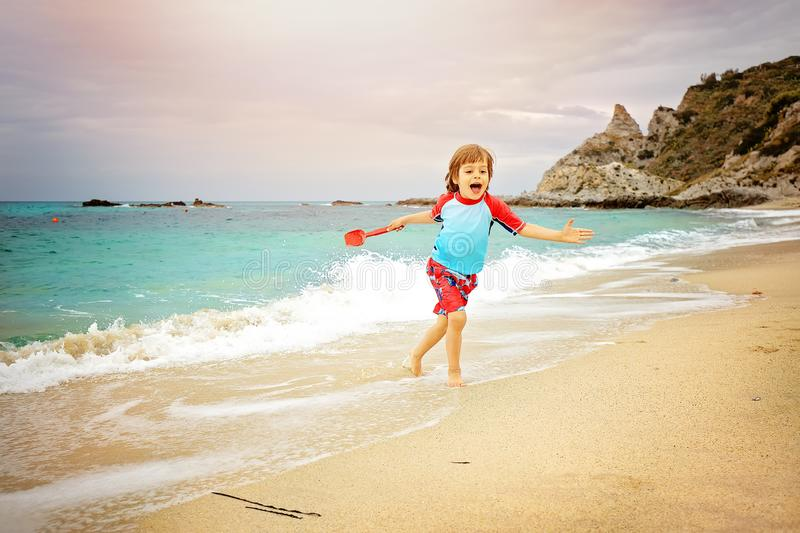 Adorable little boy having fun at the beach on vacation. Kid wearing swimming trunks and sun protection t-shot playing stock photos