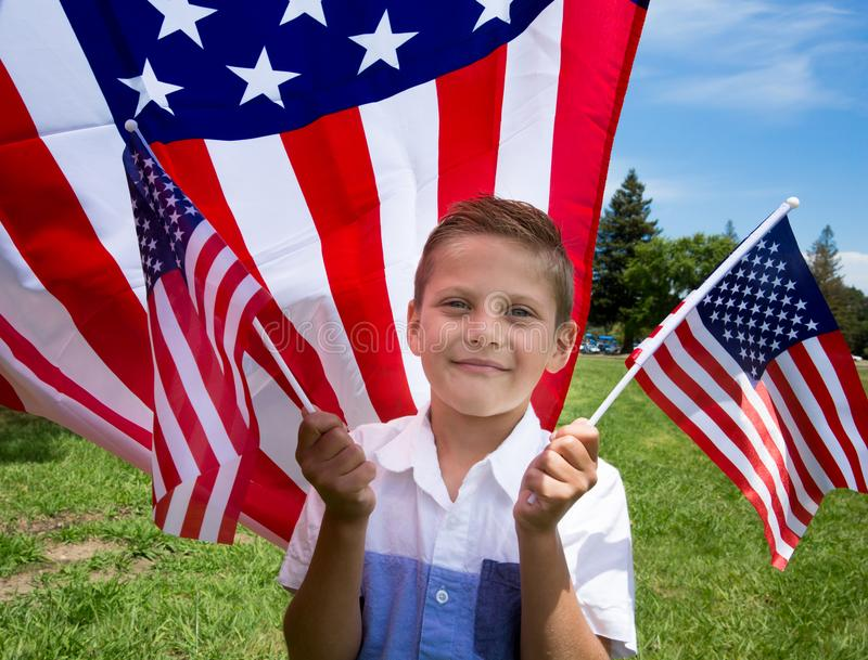Adorable little boy holding american flag outdoors on beautiful summer day royalty free stock photography