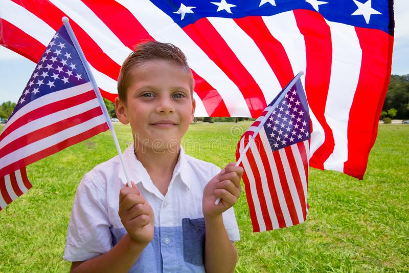 Adorable little boy holding american flag outdoors on beautiful summer day royalty free stock photo