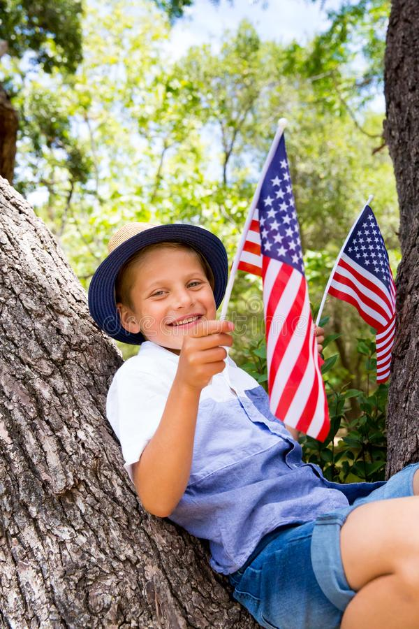 Adorable little boy holding american flag outdoors on beautiful summer day stock images