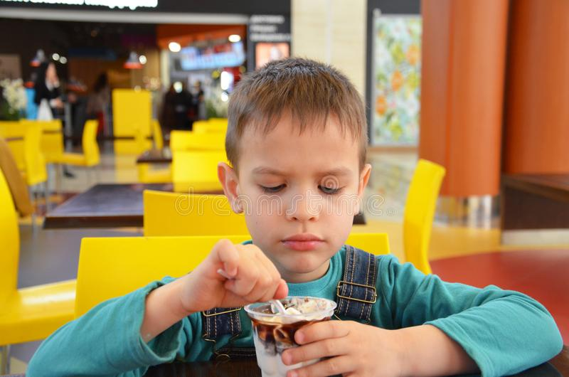 Adorable little boy in a businessman`s business suit in a hurry eating ice cream at restaurant during lunch. stock image