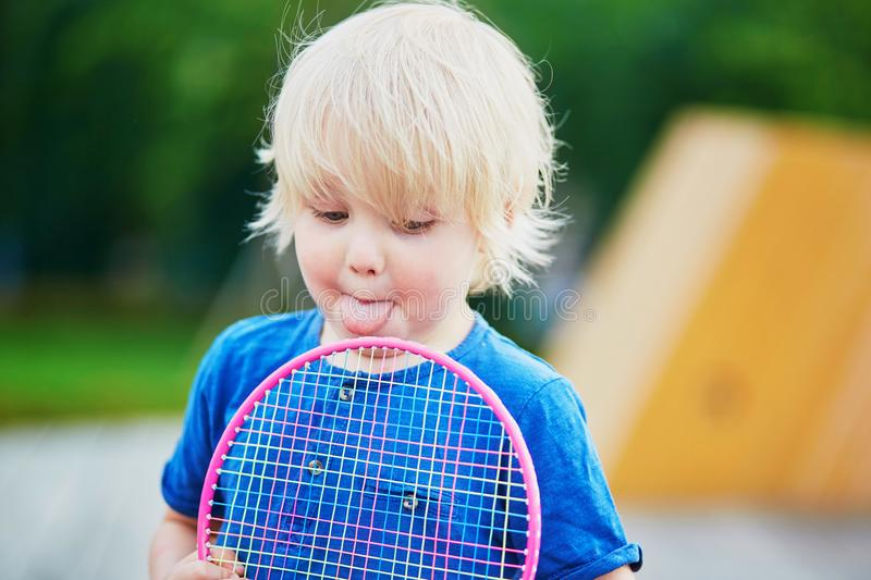 Little boy playing badminton with mom on the playground. Adorable little boy playing badminton with his mother on the playground. Outdoor summer activities for royalty free stock photo