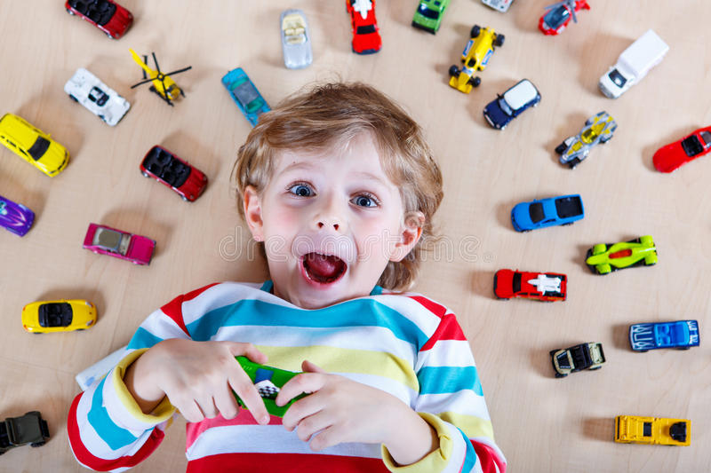 Unique Fun For Little Boys Toys : Adorable little boy playing with lots of toy cars indoor