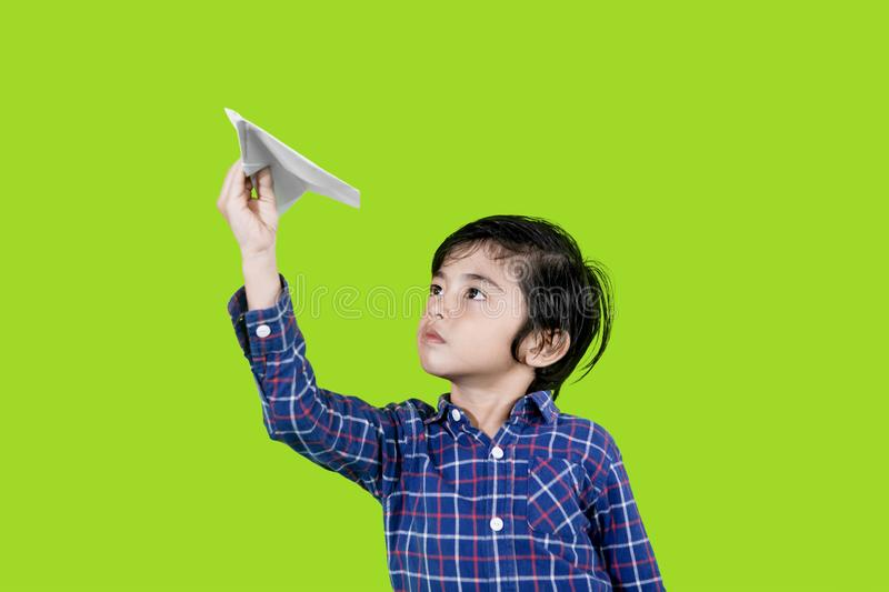 Adorable little boy playing a paper plane on studio. Picture of adorable little boy playing a paper plane while standing in the studio with green screen royalty free stock image