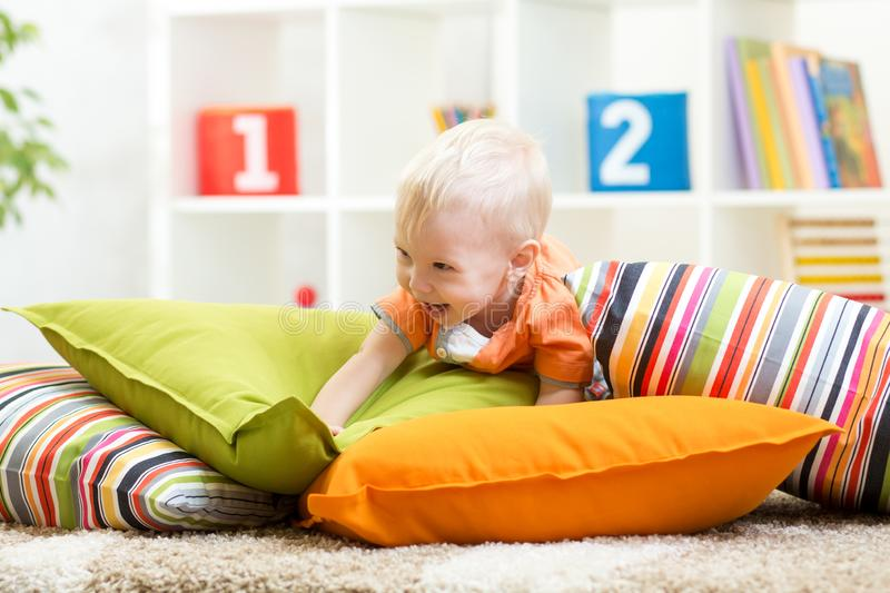 Adorable little boy playing with pillows on floor in children room royalty free stock image