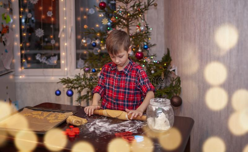 Adorable little boy is preparing the gingerbread, bake cookies in the Christmas kitchen royalty free stock image